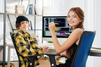 cheerful-pretty-teenage-girl-and-her-brother-smiling-at-camera-when-sitting-at-desk-and-doing-homework-for-computer-science-class
