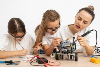 girls-and-female-teacher-doing-science-experiments-together-with-robotic-car (1)